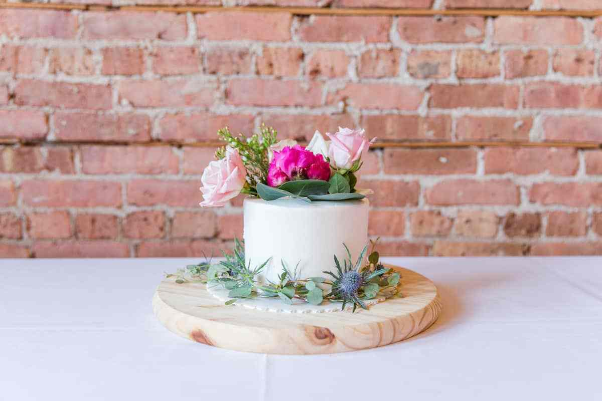 small white wedding cake decorated with eucalyptus, blue thistle, and pink rose
