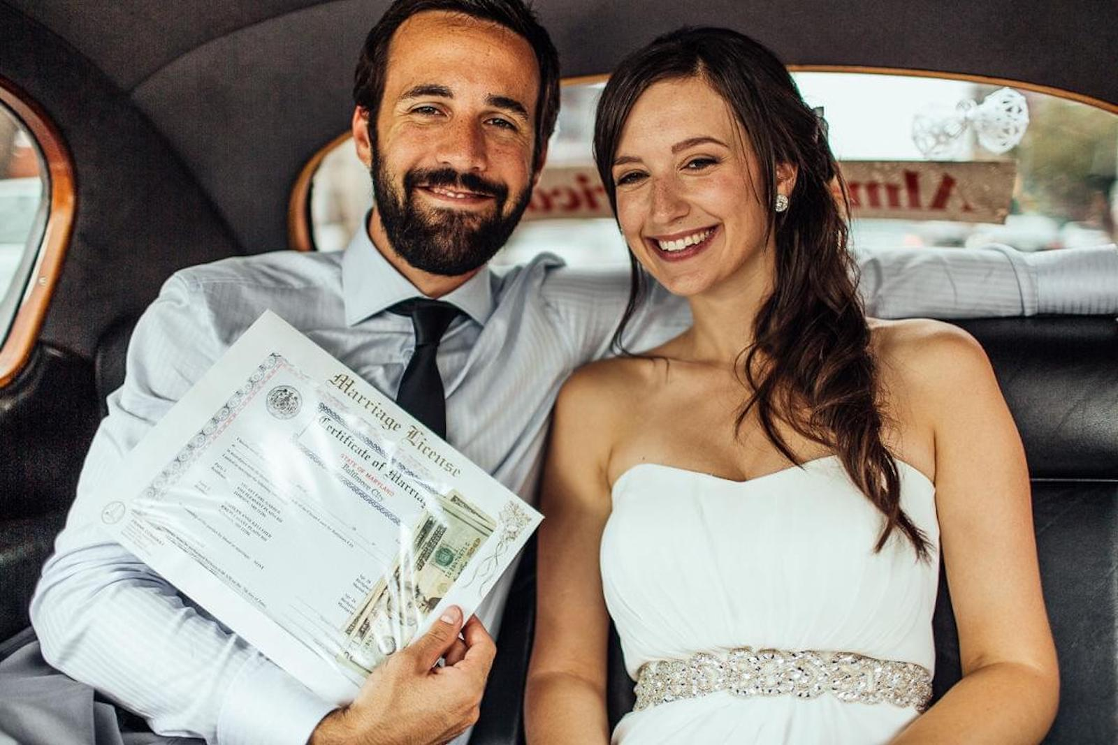 bride and groom sitting in the backseat of car posing with marriage license