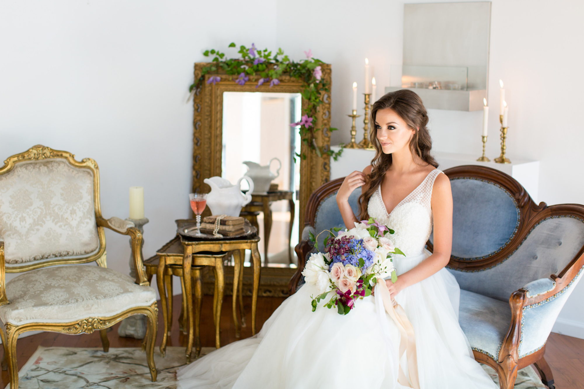 bride holding a bouquet sitting on light blue sofa in bridal suite with mirror in wooden frame in background