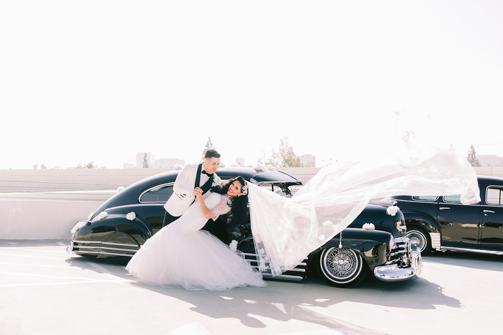bride and groom in front of black vintage car