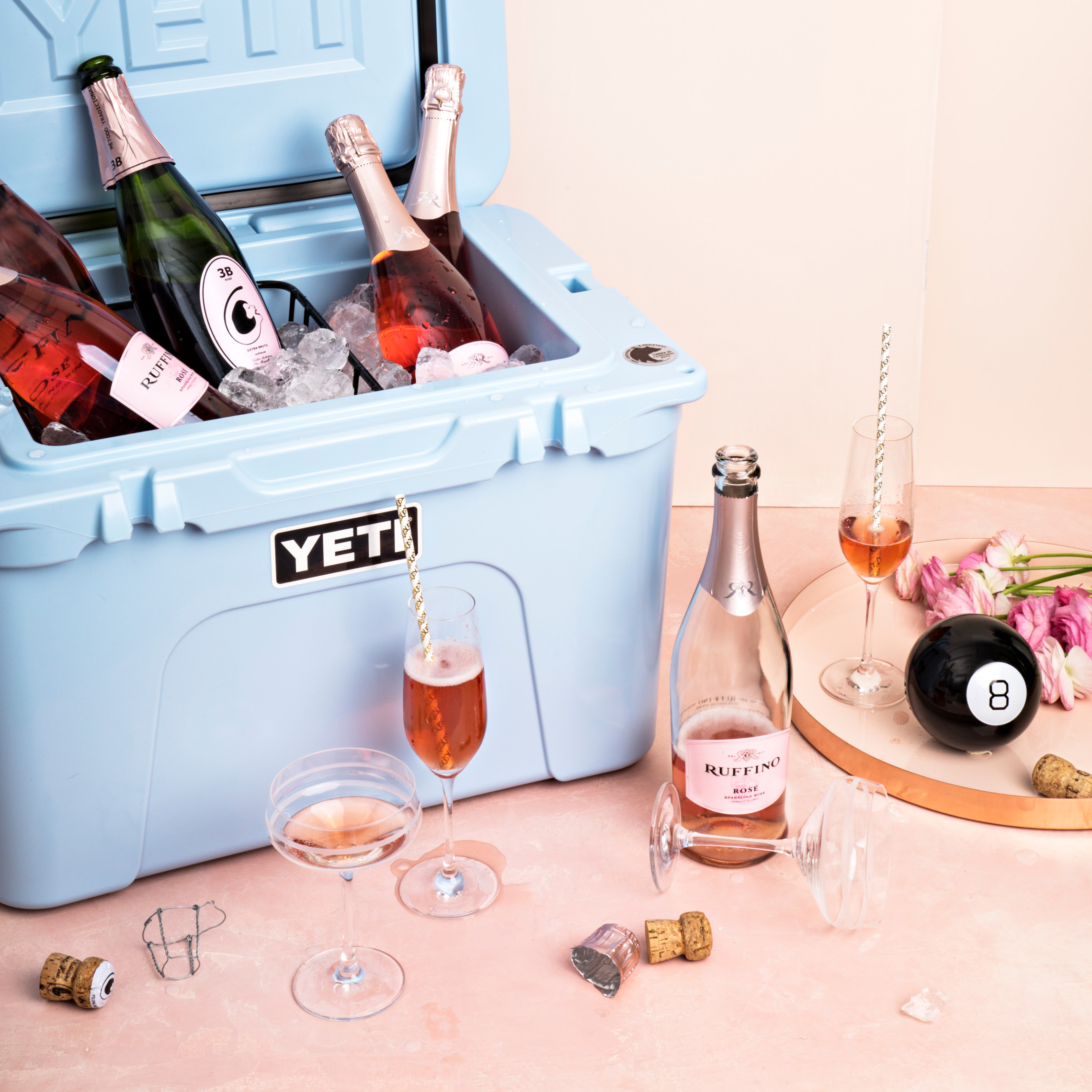 Yeti cooler filled with bottles of sparkling rose wine and glasses filled with wine in the background