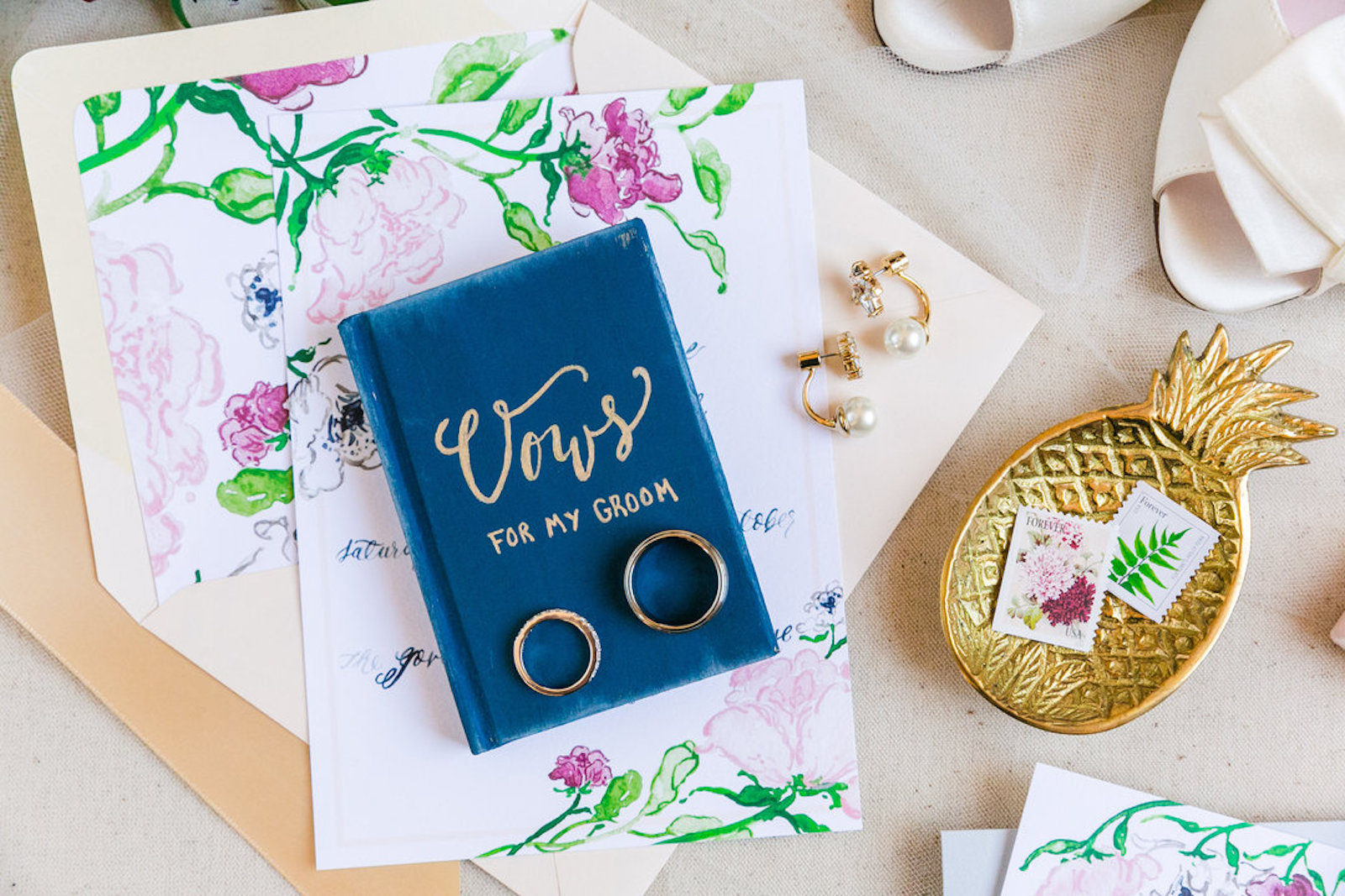 a navy book of wedding vows with gold script, with two wedding rings on top lying on pink floral invitation