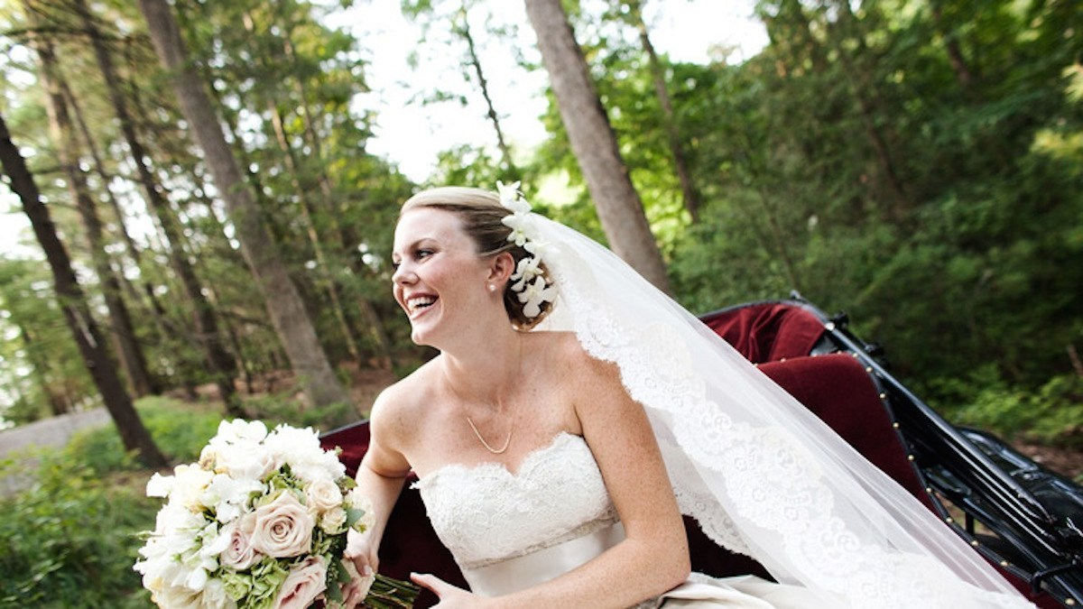 Bride with a bouquet ,smiling and sitting on a classic cart with a green outdoor