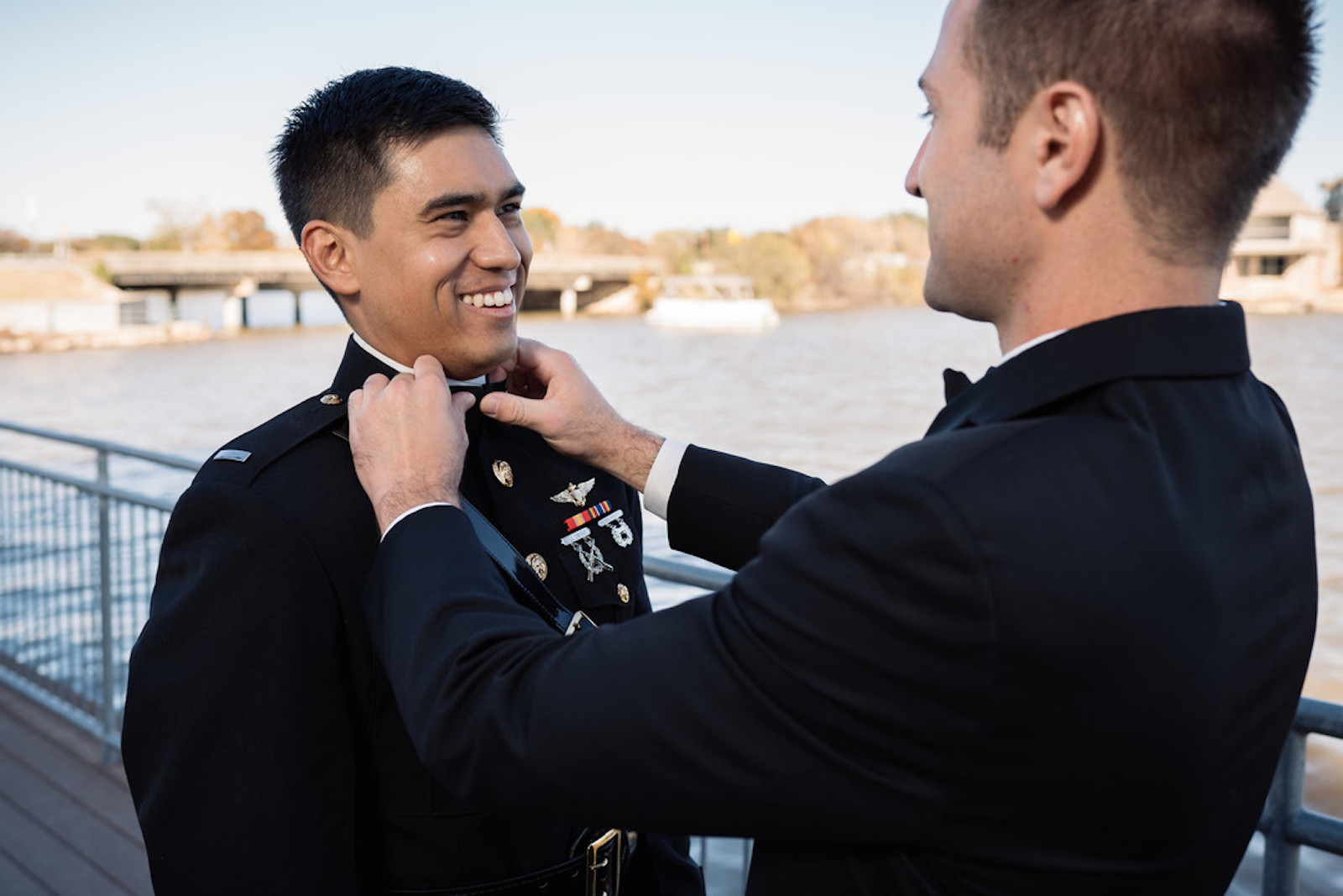 best man adjusts collar pin for groom in military attire