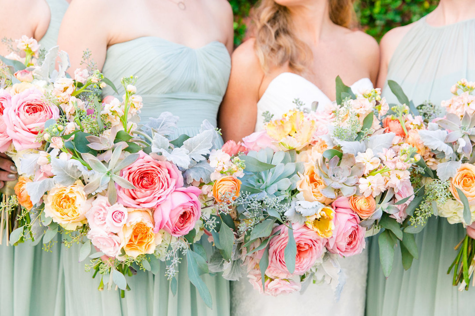 close up of bridesmaids and bride holding bouquets with peonies, roses, and greenery