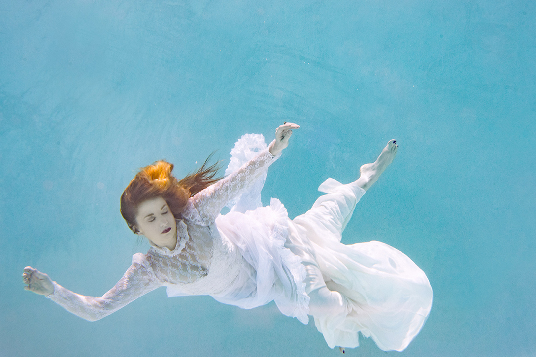 Woman in white floating underwater