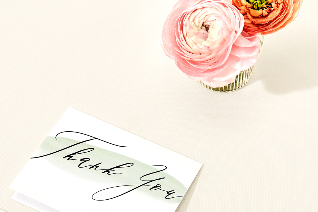 wedding thank you notes on a marble counter next to a ring dish and a vase of pink peonies