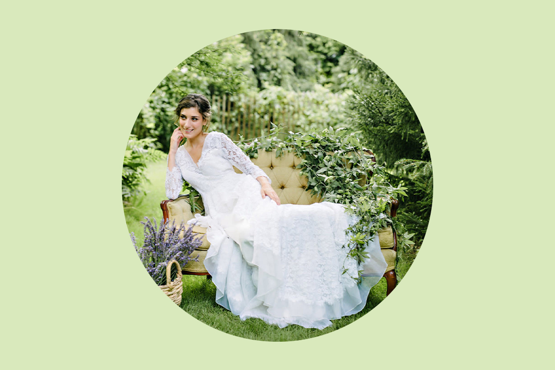 bride wearing long-sleeve lace dress sitting on a settee in the middle of a garden with a basket of cut purple lavender beside her