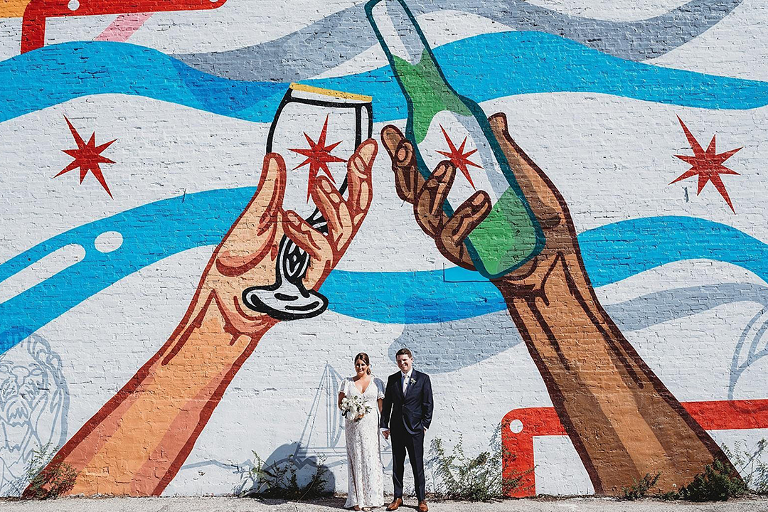 couple posed in front or mural