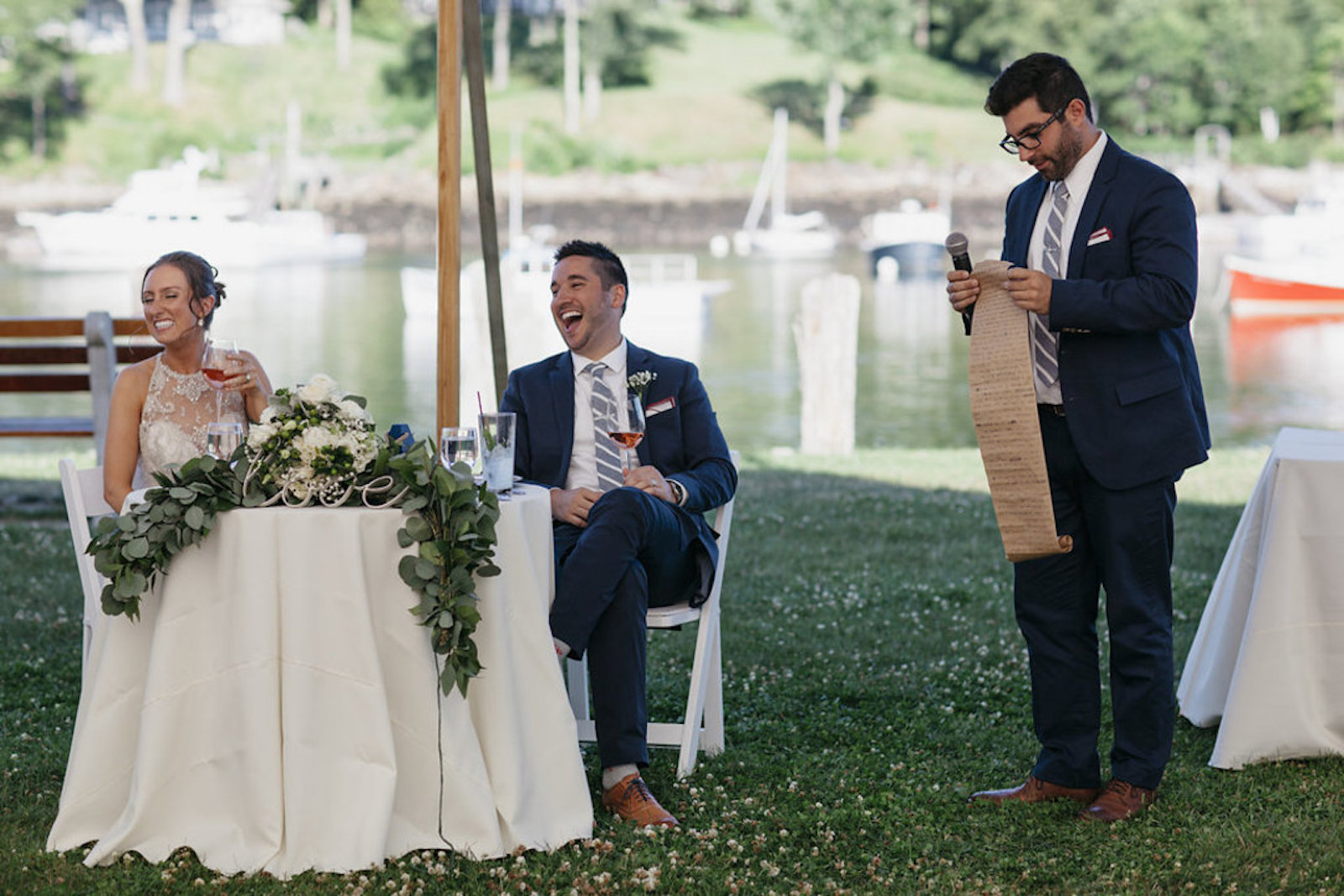 bride and groom laughing as best man gives speech at a wedding reception