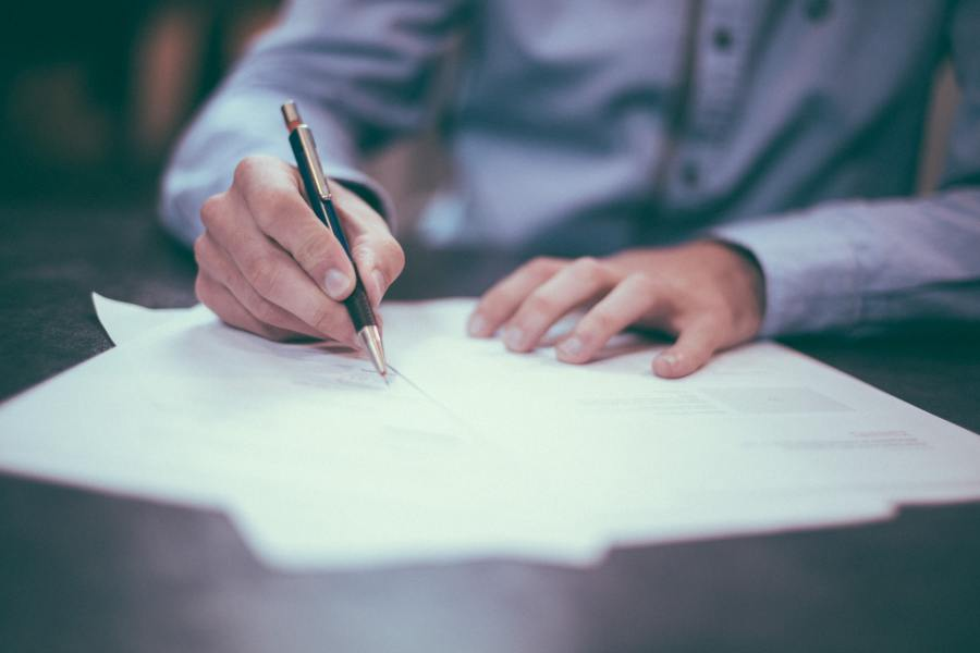 Person signing a document with a pen.