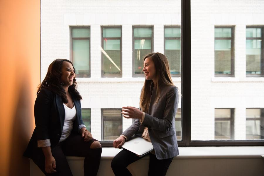 Two women having a conversation as colleagues.
