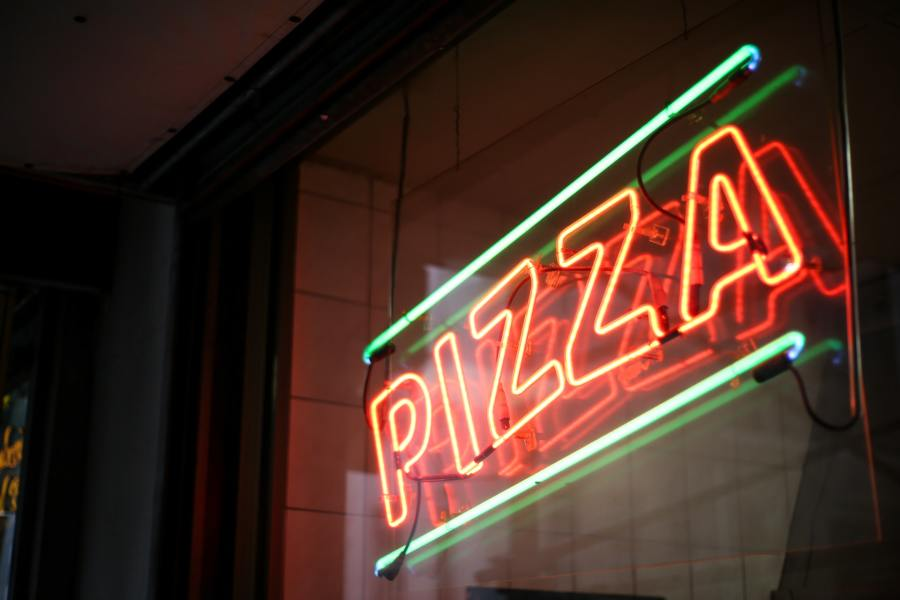 A neon sign in a restaurant window spelling the word 'pizza'.