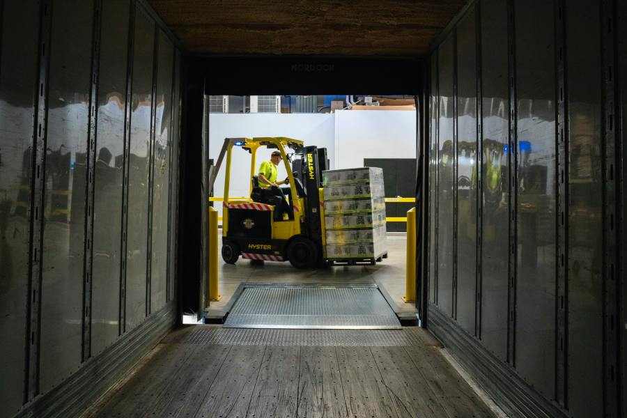 Man operates forklift in a distribution centre or storage facility.