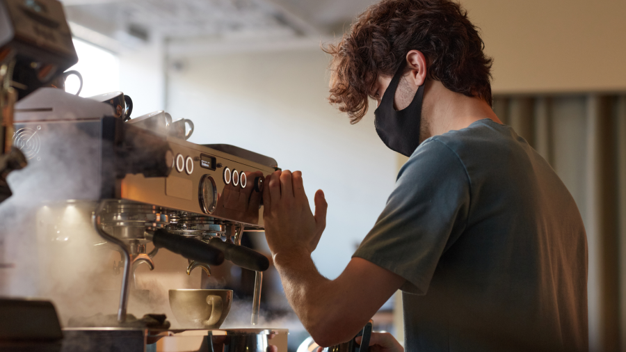 A barista working at a coffee machine in a cafe.