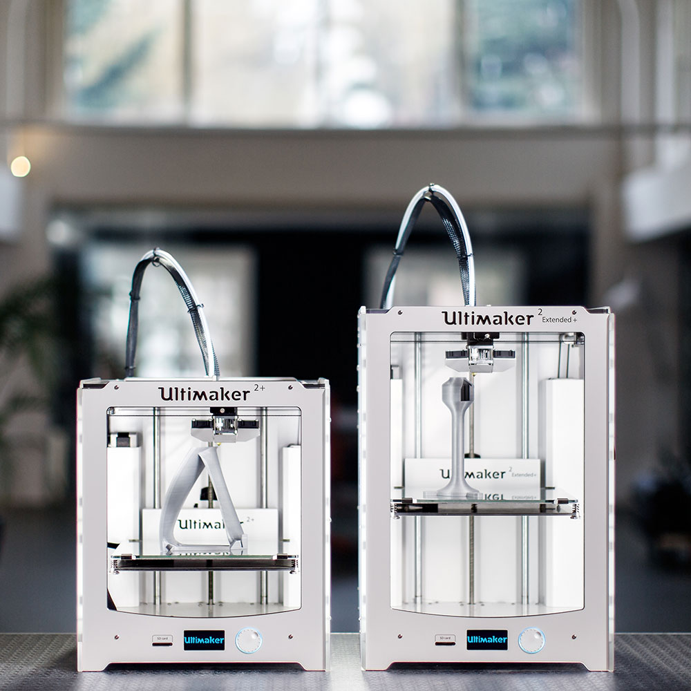 Ultimaker 2+ and Ultimaker 2 Extended+ sitting on a desk in a studio