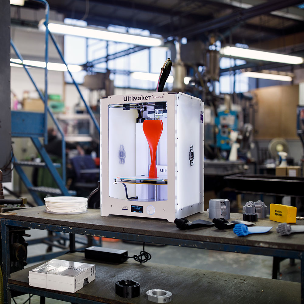 Ultimaker 2 Extended+ on an industrial workbench printing a tall red propeller