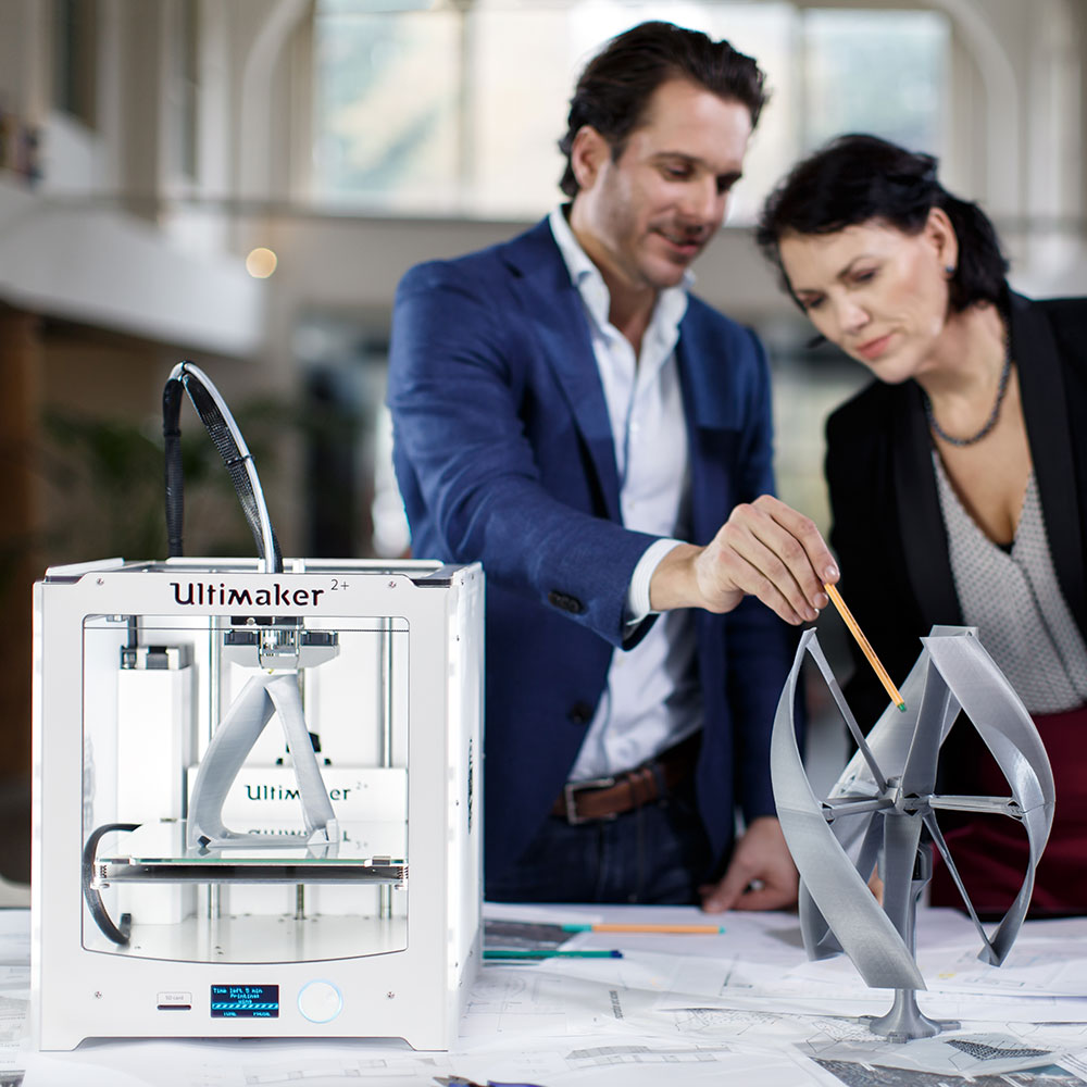 Two designers discussing a model printed on Ultimaker 2+ with its open filament system