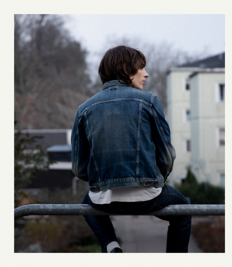 Guy in denim jacket sitting on a fence.