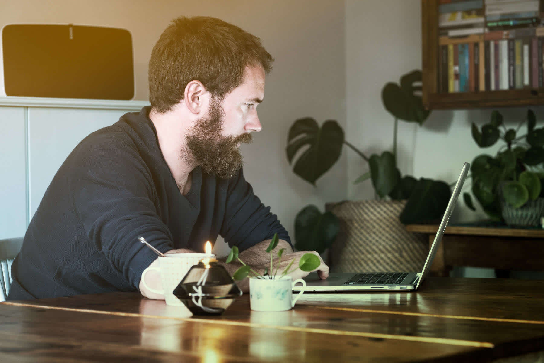 A man is sitting at a kitchen table working on his computer.