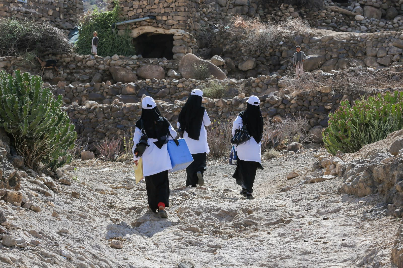 Health workers make their way to deliver polio vaccines to the remote village of Bani Mansour