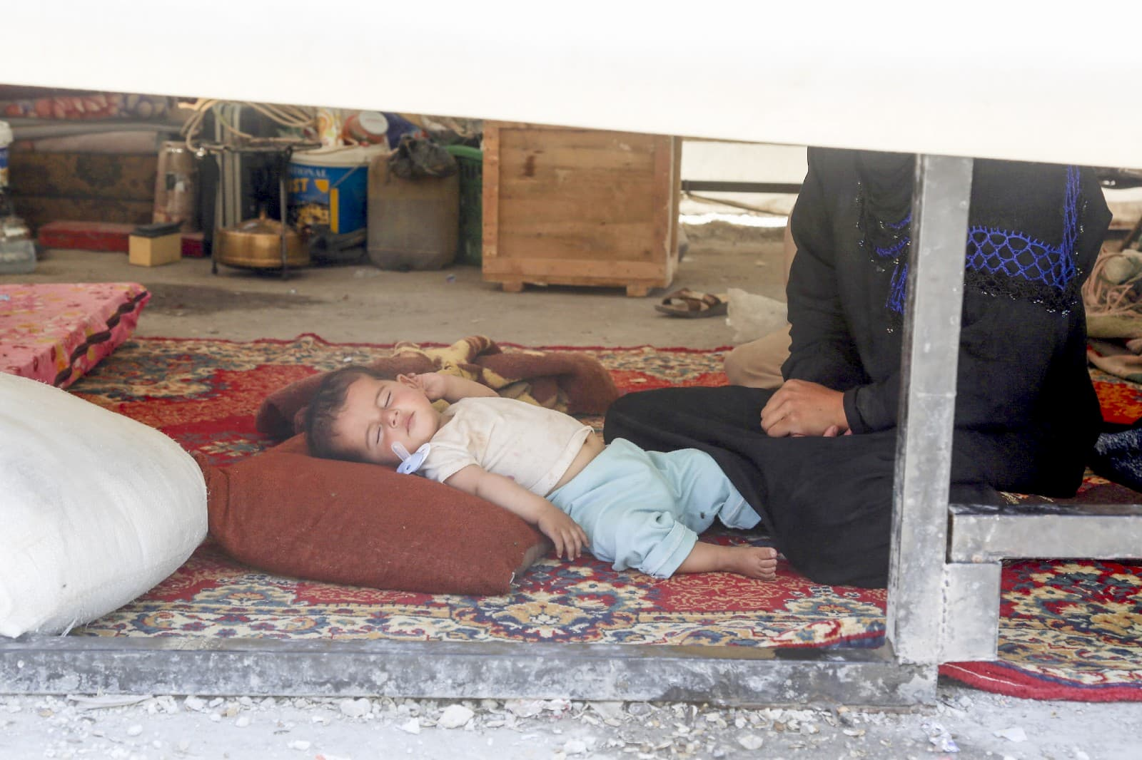 A baby sleeps in his family's tent in Ain Issa makeshift camp, northeastern Syria