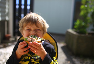 Child bites into sandwich