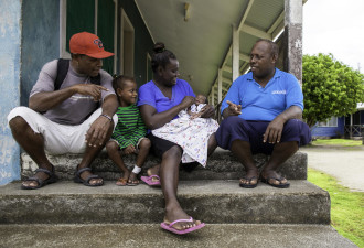 Paul Maesiala talks with a family in the Solomon Islands