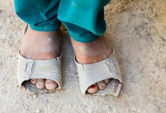 Shahnaz, (9) from Afghanistan shows her sandal to the camera.