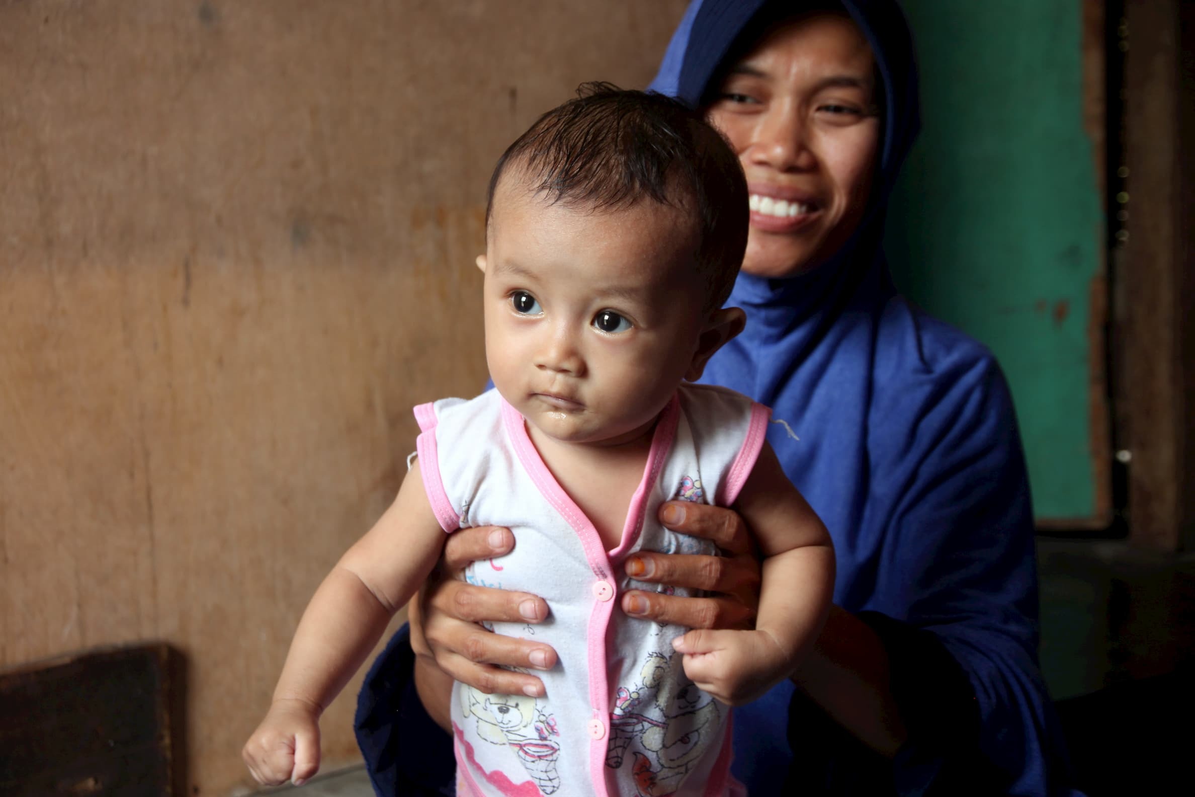 Mother Sarifah holds Baby Luthfi.