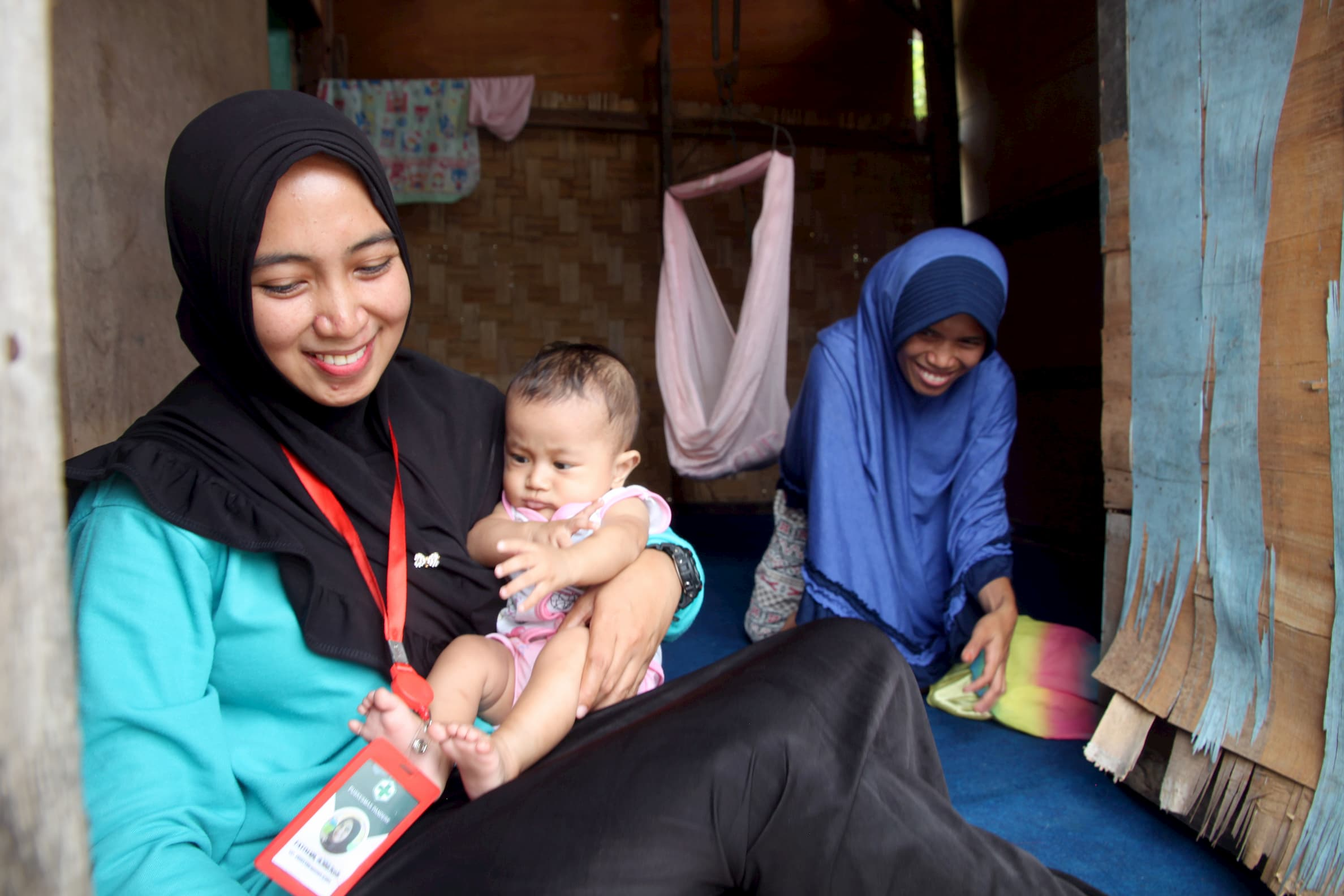 Midwife Fatimah holds baby Luthfi