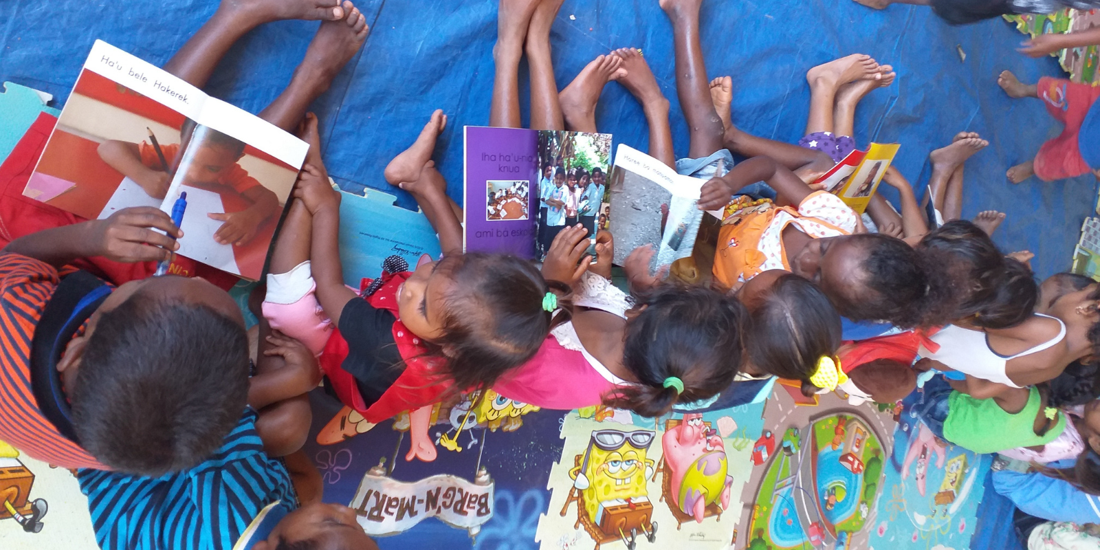 Children are excited to read a book in Tetun (one of Timor-Leste's national languages
