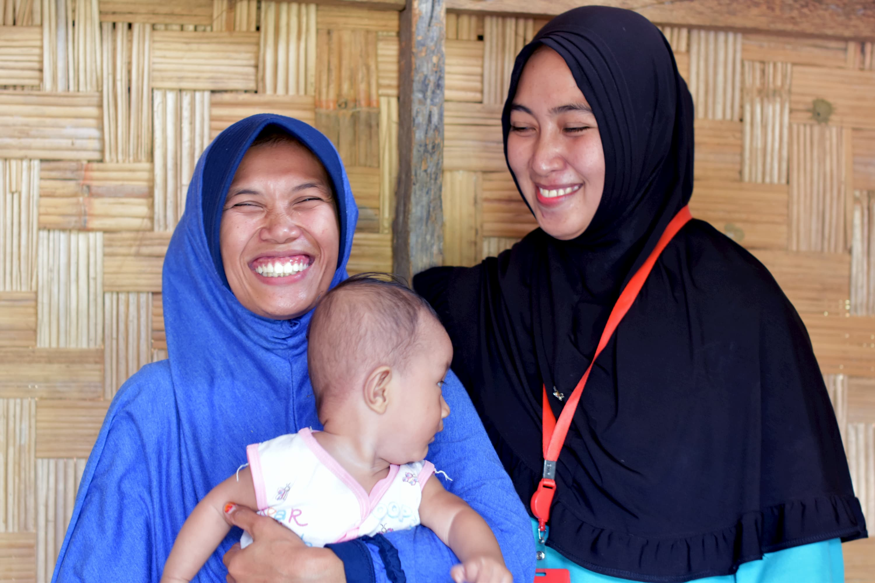 Midwife Fatimah with mother Sarifah and her six-month old son Luthfi.