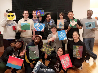 Members of the community in San Francisco showing off their creations after a wine and paint night.