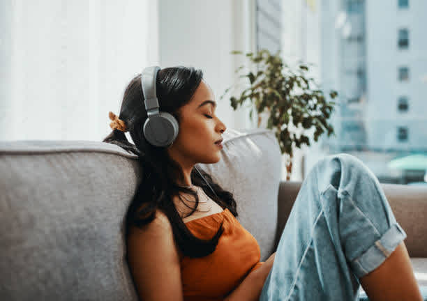 Image of a woman listening to music on headphones.