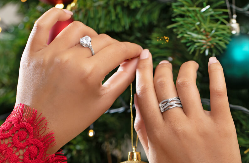 Woman's hands decorating christmas tree whilst wearing Michael Hill sterling silver rings