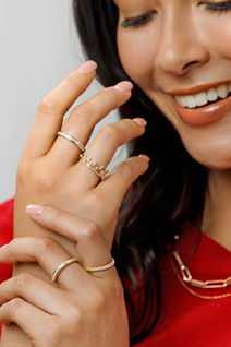 Gold Rings on hand of lady wearing red blouse