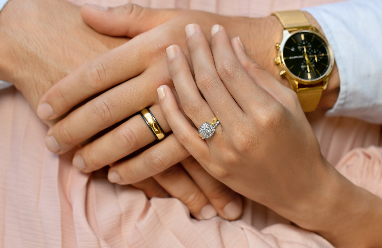 Couple holding hands wearing Titanium and Yellow Gold Band and Diamond Cluster engagement ring at Michael Hill