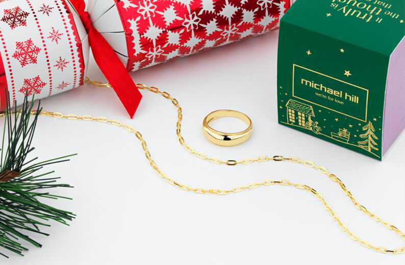 Gold Chain and Gold Ring surrounded by christmas cracker