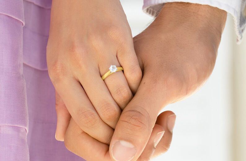 Couple holding hands whilst wearing diamond solitaire engagement ring from Michael Hill