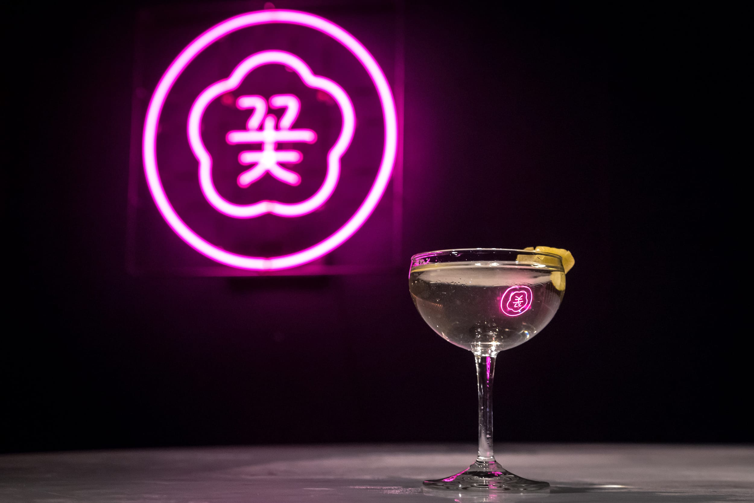 Cocktail sitting on a table with a pink neon sign of the Cote logo in the background