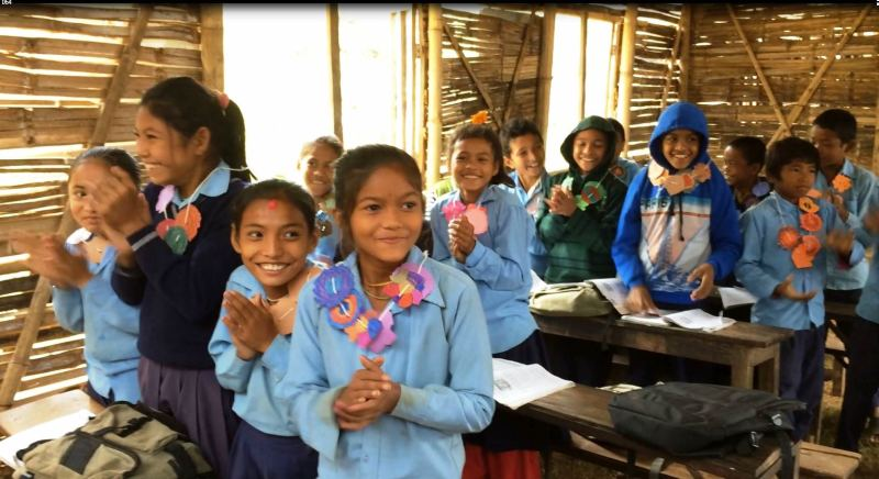 Students in Nepal receiving paper flower garlands made during the Challenge and delivered by Save the Children!