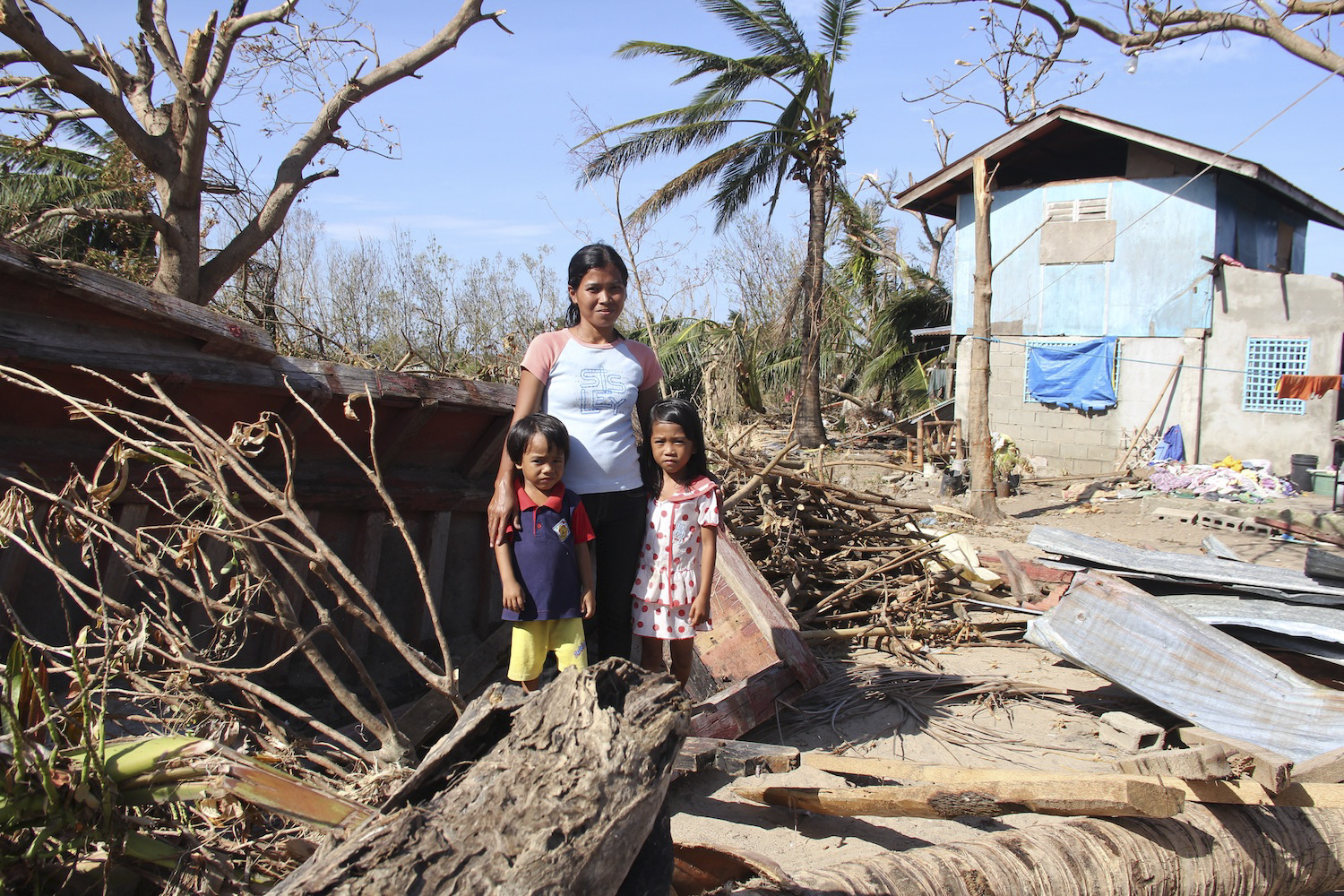 A family amidst devastation from Typhoon Haiyan.