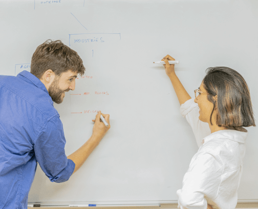 A man with a beard and a blue shirt with rolled up sleeves and a woman with short hair, a white shirt with rolled up sleeves drawing on a white board and smiling at each other.