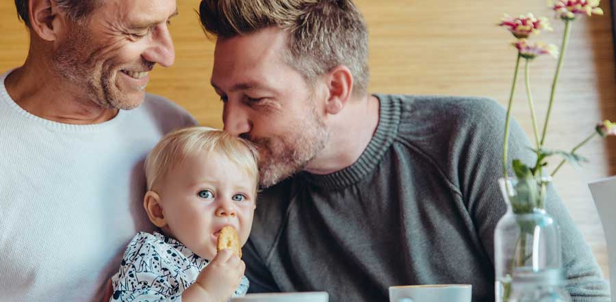 Baby being kissed by dads at breakfast table
