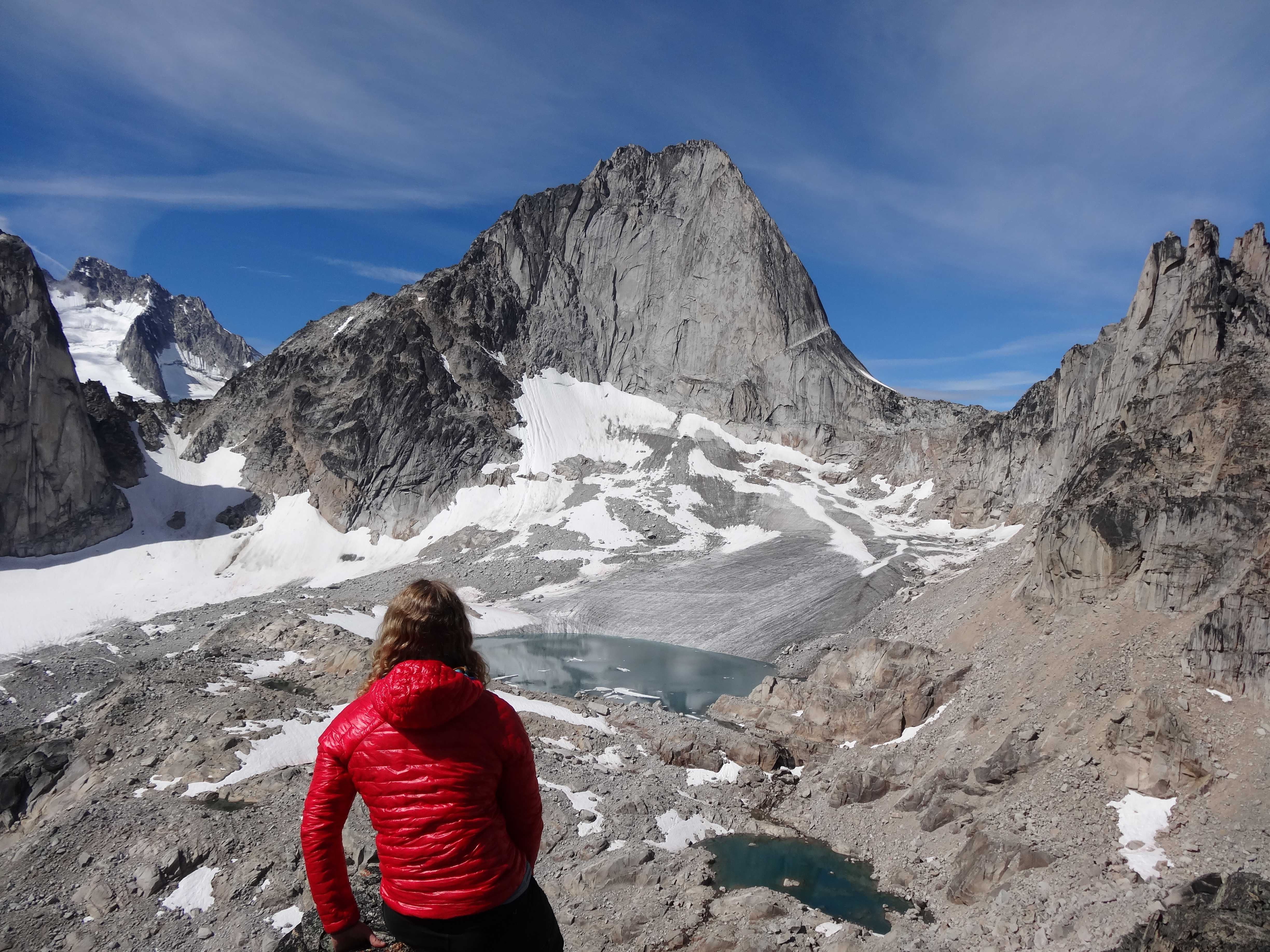 Woman In Red Coat Looking At A Glaciated Alpine Peak