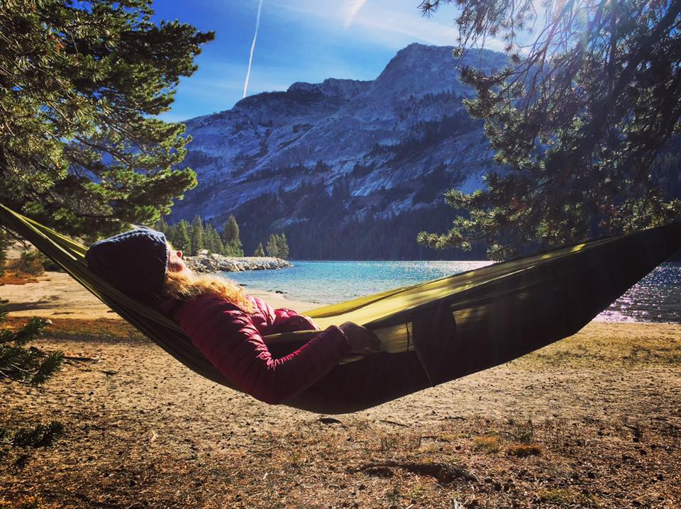 Female Climber Relaxing In Hammock Overlooking Mountain Lake