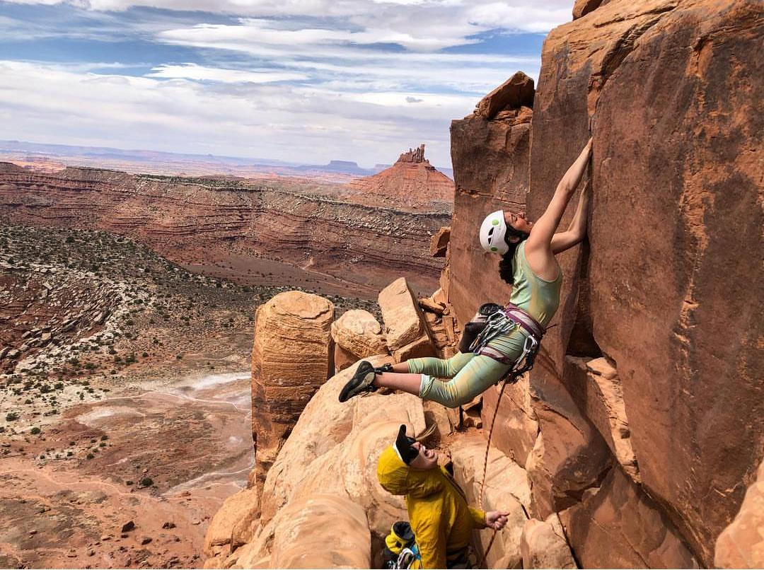 Female Climber Making A Dynamic Move Whilst Crack Climbing