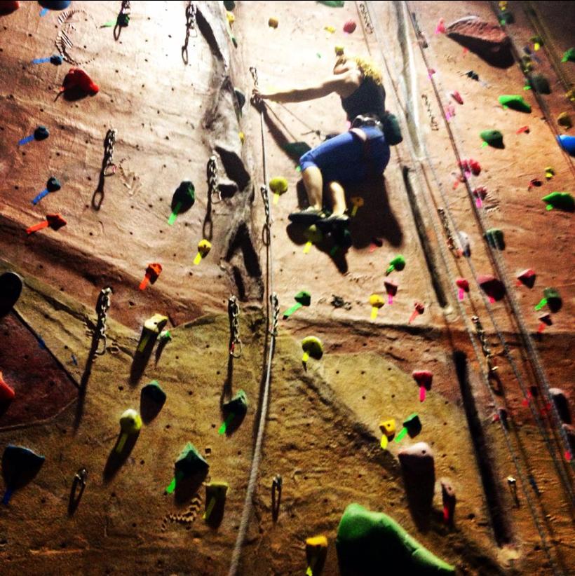 Woman Climbing On Indoor Climbing Wall