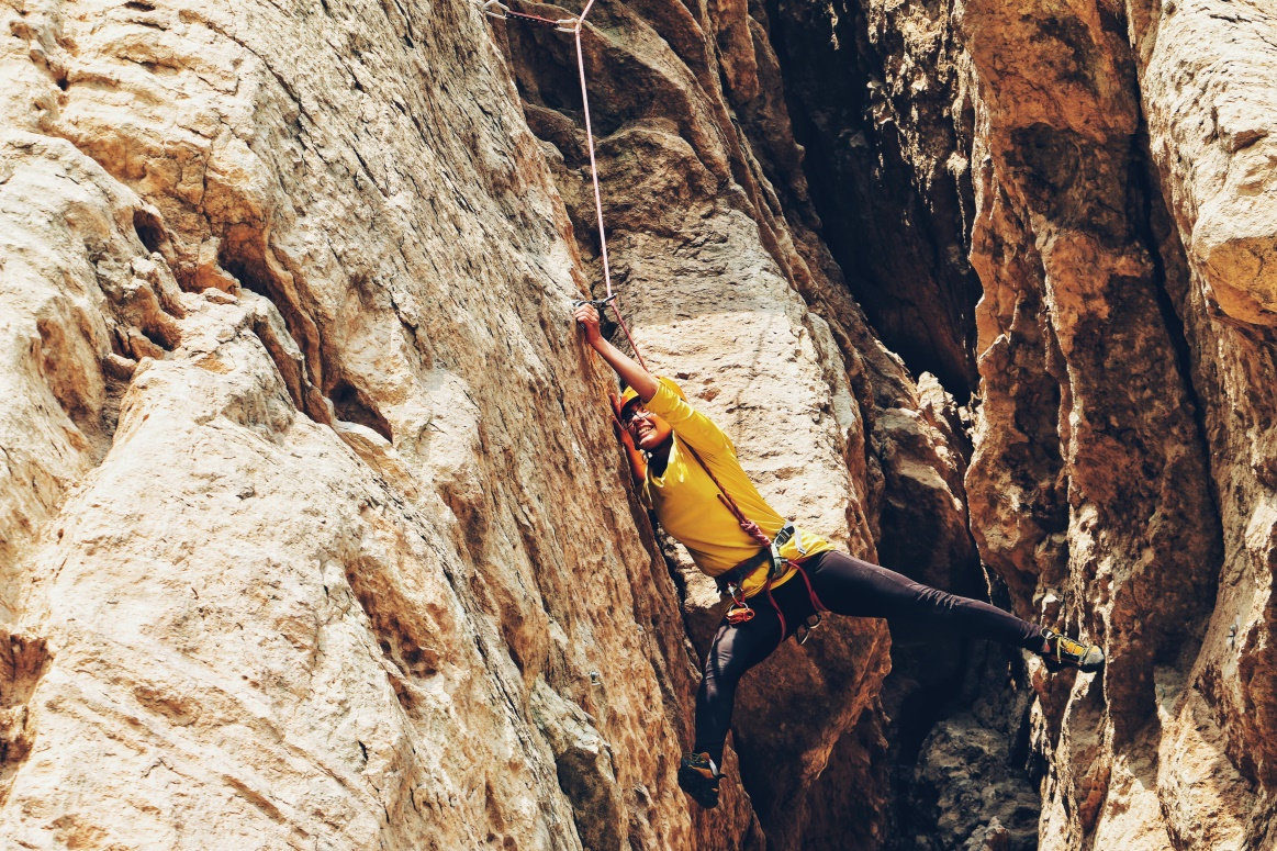 Female Rock Climbing Bridging And Reaching For Next Hold